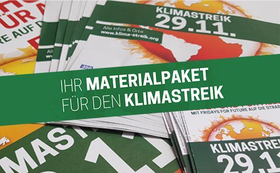 Flyer, Poster und Aufkleber für den Klimastreik liegen auf einem Tisch. Darüber steht: Ihr Materialpaket für den Klimastreik